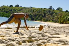 Fattig malagasy pojke som bryter kokosnötter på stranden fotografering för bildbyråer