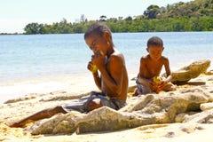Fattig malagasy pojke som bryter kokosnötter på stranden arkivfoton