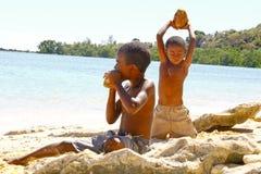 Fattig malagasy pojke som bryter kokosnötter på stranden royaltyfria bilder