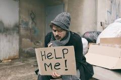 Fattig man med HJÄLP MIG för att underteckna på förrådsplatsen royaltyfri fotografi