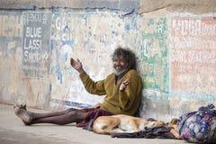 Fattig man och hund i Varanasi, Indien Arkivbilder