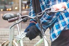 Fattig man som låser hans cykel på gatan av Toronto royaltyfria bilder
