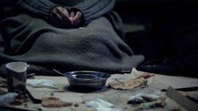 Fattig person i den sittande framdelen för smutsig torkduk av bunken som bor på gatan, hemlöshet royaltyfria bilder