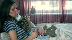 Fattig sjuk barnflicka med den flotta den björnvännen och modern som tillsammans sitter i säng stock video