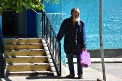 Fattiga homless arbetslösa gamal mankostnader på en ingång som shoppar royaltyfria bilder