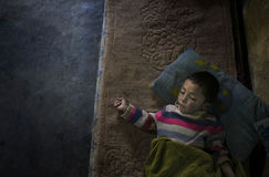 Fattigt barn som sover på morförälderhusgolv Fotografering för Bildbyråer