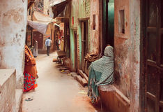 Fattigt folk i långa traditionella halsdukar som sitter på grungegatan av den forntida indiska staden Royaltyfri Fotografi