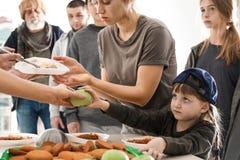 Fattigt folk som mottar mat fr?n volont?rer arkivfoto