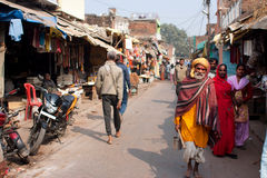 Fattigt hinduiskt folk som går på den indiska gatan på den härliga soliga dagen, Indien arkivbild