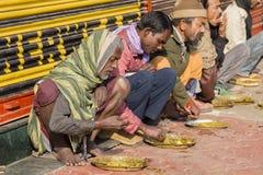 Fattigt indiskt folk som äter fri mat på gatan i Varanasi, Indien Fotografering för Bildbyråer