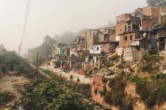 Fattigt område av Haridwar, Indien Fattigt folk för hus på backen framme av en smutsig flod royaltyfri fotografi