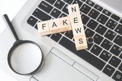 Fatto di ricerca o concetto falso, cubo di legno di vibrazione della mano cambiare la parola su lantop, lente Giorno degli sciocc immagine stock