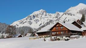 Fattoria nelle alpi svizzere e nelle montagne innevate Immagini Stock