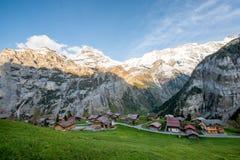 Fattoria in villaggio con la montagna svizzera della neve delle alpi nel fondo Fotografia Stock Libera da Diritti