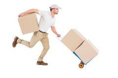 Fattorino con il carrello di correre delle scatole Fotografia Stock