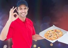 Fattorino felice che sega la pizza Illumina la priorità bassa fotografie stock