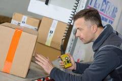 Fattorino in scatole di cartone di caricamento del magazzino nel camion fotografie stock