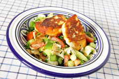 Fattoush with fried haloumi. A bowl full of fattoush Middle Eastern salad topped with fried haloumi cheese. Fattoush is made with fried or toasted flat bread Stock Image