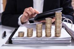 Fattura calcolatrice della donna di affari con le monete impilate fotografia stock libera da diritti