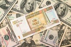 Fattura dei pesi cubani sopra parecchie banconote in dollari Fotografia Stock Libera da Diritti