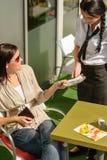 Fattura di pagamento della donna al ristorante del caffè della cameriera di bar Fotografia Stock