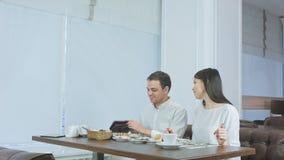Fattura di pagamento felice delle coppie portata dal cameriere e lasciare caffè Fotografie Stock Libere da Diritti