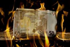 Fattura di soldi dell'euro 50 su legno appena circa da bruciare Fotografia Stock