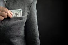 Fattura di soldi nascondentesi dell'uomo d'affari in tasca con lo spazio della copia Fotografia Stock