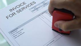 Fattura per servizio pagato, mano che timbra guarnizione sul documento commerciale, affare archivi video