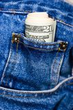 Fatture del dollaro in blue jeans Fotografia Stock