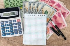 100 fatture del dollaro, dell'euro e di yuan con il blocco note ed il calcolatore Immagini Stock Libere da Diritti