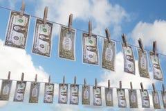 Fatture del dollaro sulla riga dei vestiti Fotografia Stock
