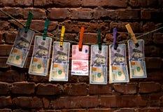 Fatture dell'euro e del dollaro che appendono su una corda Fotografia Stock Libera da Diritti