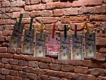 Fatture dell'euro e del dollaro che appendono su una corda Fotografia Stock