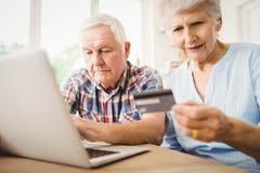 Fatture di pagamento senior delle coppie online Fotografia Stock