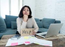 Fatture di pagamento sollecitate ed enormi di finanze della casa di contabilit? della giovane donna che chiedono l'aiuto fotografie stock