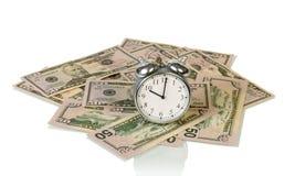Fatture di soldi con l'orologio Immagini Stock
