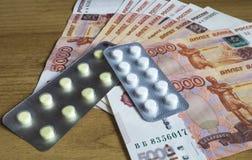 Fatture di soldi con la compressa medicinale Fotografie Stock Libere da Diritti