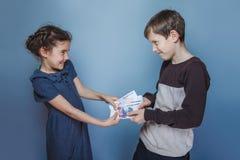 Fatture di soldi della tenuta della ragazza e dell'adolescente nel suo Fotografia Stock