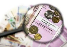 Fatturi per il pagamento con le monete e le fatture attraverso un gl d'ingrandimento Immagini Stock