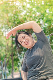 Fatty asian white girl warming body, exercise. Royalty Free Stock Images