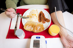 Fatty Breakfast While Monitoring Blood Pressure. Woman eats a high cholesterol and fatty breakfast consisting of fried eggs, buttered toast, bacon, and orange Royalty Free Stock Photos