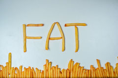 Fatty french fries on white background. French fries forming word fat on a white background Royalty Free Stock Photos