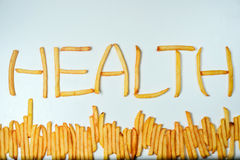 Fatty french fries on white background. French fries forming word health on a white background Stock Images