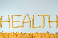 Fatty french fries on white background. French fries forming word health on a white background Stock Photos