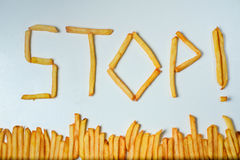Fatty french fries on white background. French fries forming word stop on a white background Royalty Free Stock Photography
