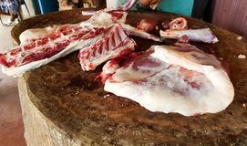 Fatty red meat cut manually on a wooden platform by a butcher with a meat copper knife.  stock image