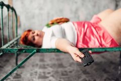 Fatty woman with sandwich in hands watches TV. Fatty woman with sandwich in hands liying on the bed and watches TV, laziness, bulimic and overweight. Unhealthy Royalty Free Stock Photography
