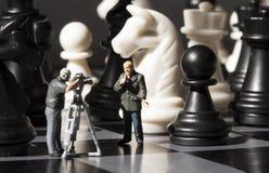 Fatura da notícia da xadrez Processo do jogo de xadrez do película Journalistas diminutos no tabuleiro de xadrez Fotografia de Stock