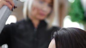 A fatura de pulverização do pulverizador de cabelo do cabeleireiro profissional do close-up fixa o penteado para o cliente fêmea filme